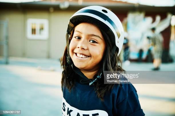 Portrait of young female skateboarder at summer skate camp
