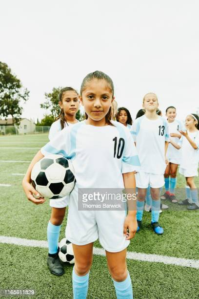 Portrait of young female soccer player holding ball and standing in front of teammates