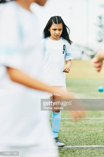 portrait of young female soccer player waiting to run warm up drills on field - trainingsdrill stock-fotos und bilder