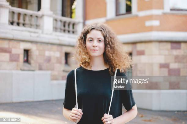portrait of young female student standing outside university - waist up stock pictures, royalty-free photos & images
