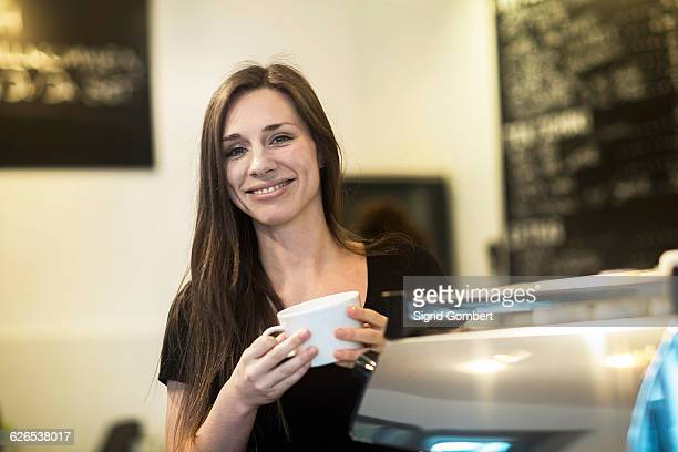 portrait of young female waitress holding coffee cup in cafe - sigrid gombert stock pictures, royalty-free photos & images