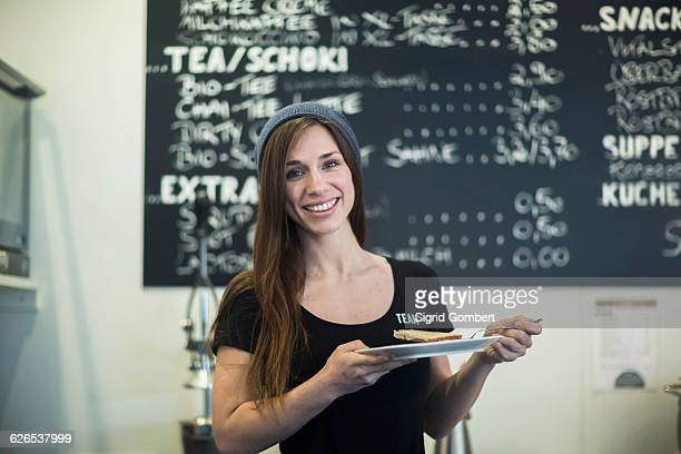 Portrait of young female waitress holding plate and cake slice in cafe