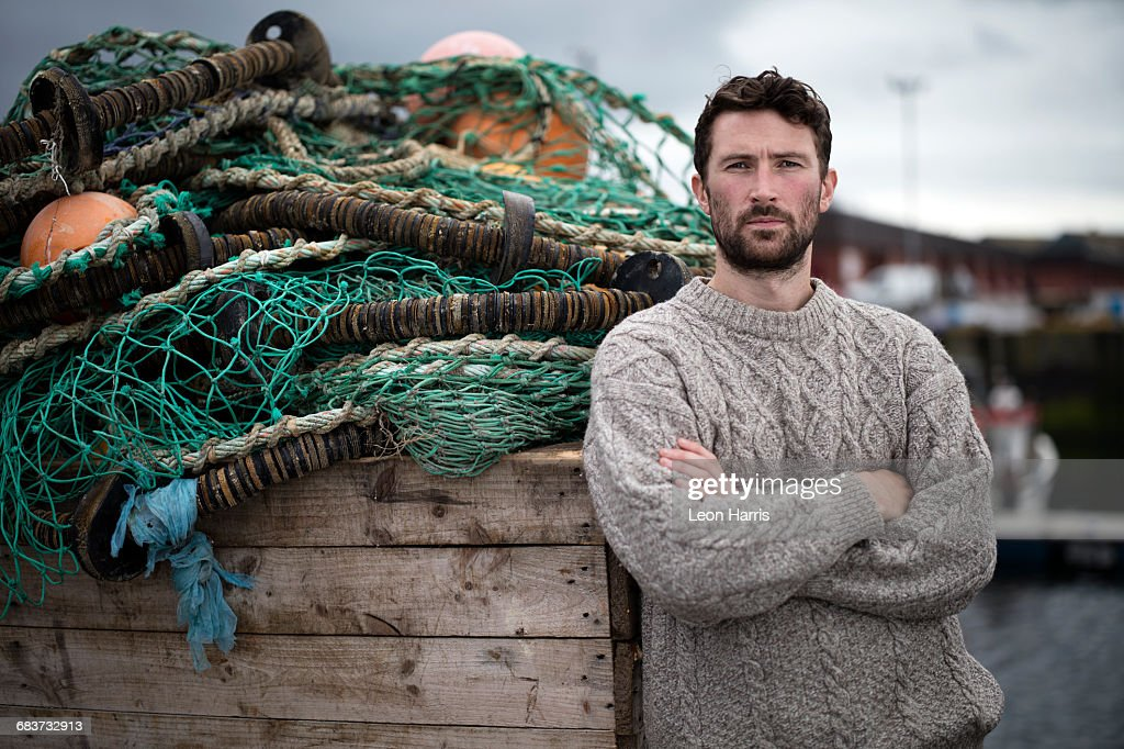 Portrait of young fisherman leaning against crate of fishing nets in harbour, Fraserburgh, Scotland : Bildbanksbilder