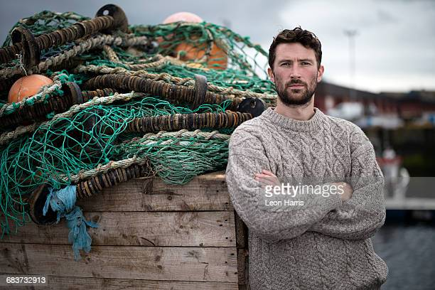 Portrait of young fisherman leaning against crate of fishing nets in harbour, Fraserburgh, Scotland