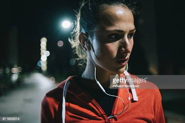 Portrait of young fitness woman in park at night