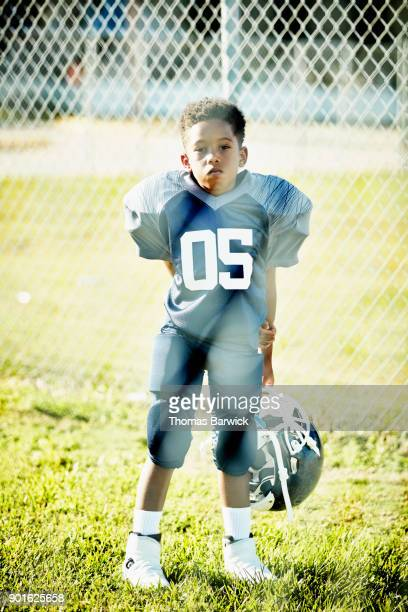 Portrait of young football player dressed for game waiting behind fence