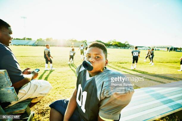 Portrait of young football player sitting on bench after football practice