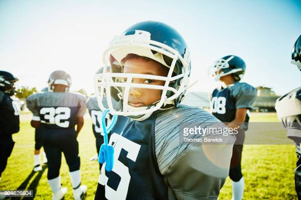 portrait of young football player standing on field with teammates before game - childhood stock pictures, royalty-free photos & images