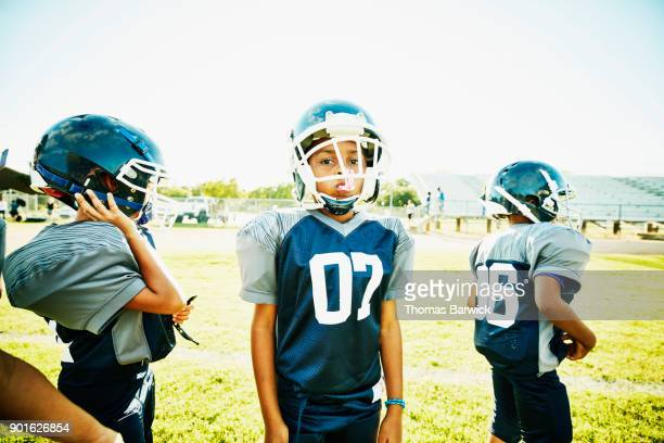 Portrait of young football player standing with teammates during practice