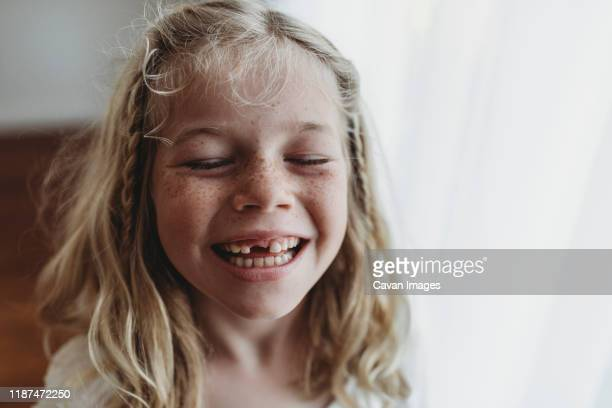 portrait of young freckled smiling girl missing tooth with eyes closed - zahn stock-fotos und bilder