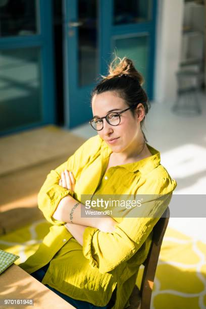 portrait of young freelancer sitting at desk in her studio - vertikal stock-fotos und bilder