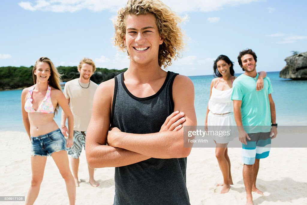 Portrait of young friends standing on beach : Stock Photo
