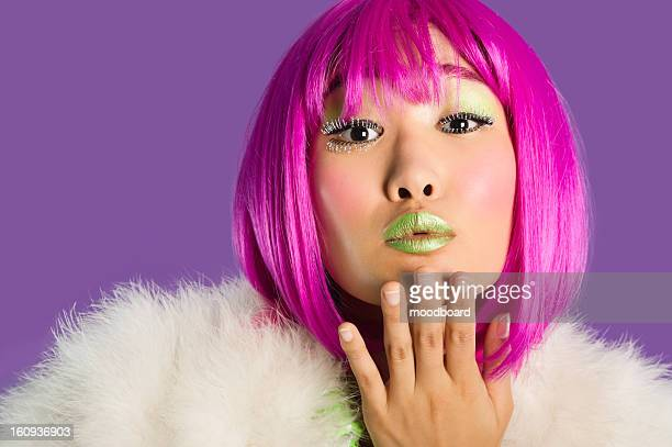 portrait of young funky woman in pink wig blowing kiss over purple background - つけまつげ ストックフォトと画像