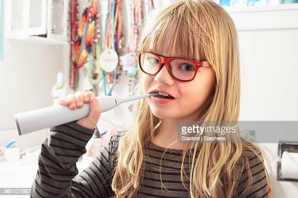 Portrait of young girl brushing teeth