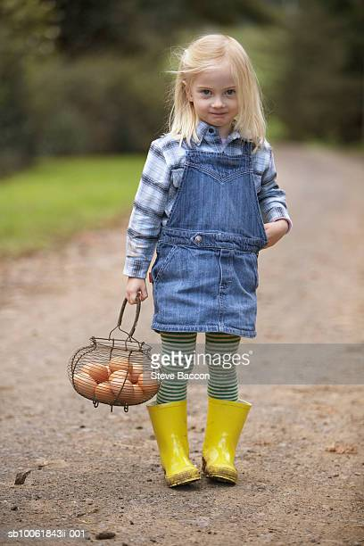 Portrait of young girl (3-4) carrying basket with eggs