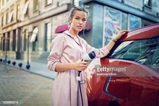 portrait of young girl charging her electric car in the city - electric car stock photos and pictures