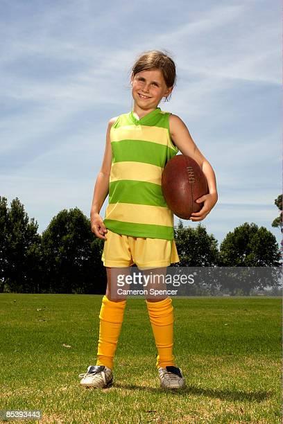 Portrait of young girl holding Australian football