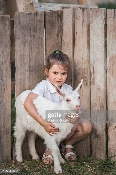 Portrait of young girl holding baby goat in park