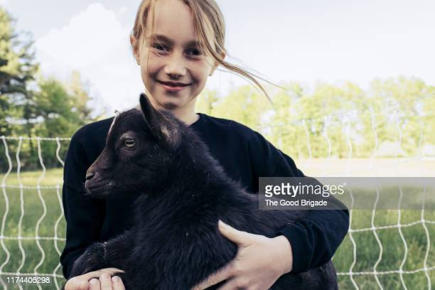 Portrait of young girl holding baby goat