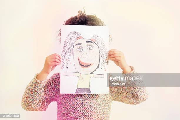portrait of young girl, holding drawing, covering face - artistic product stock pictures, royalty-free photos & images