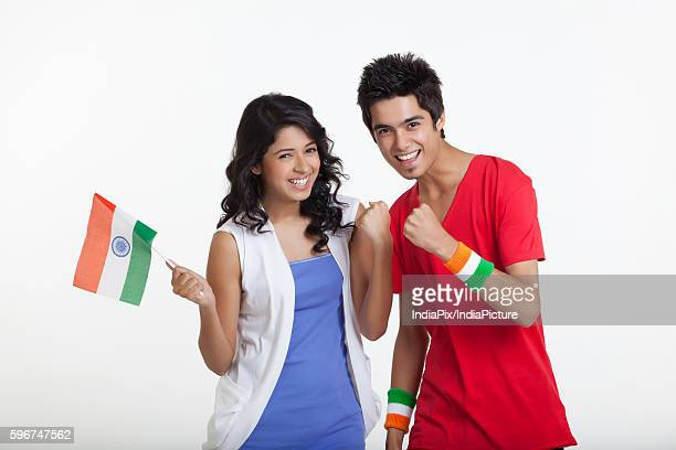 Portrait of young girl holding Indian flag while cheering with friend over white background