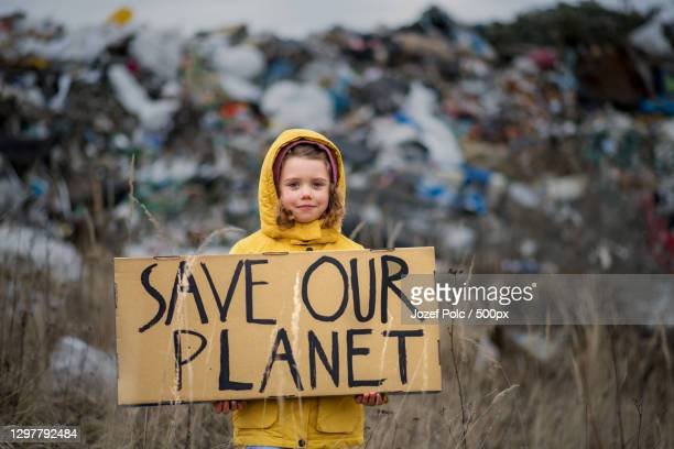 portrait of young girl holding save our planet sign against landfill - aktivist stock-fotos und bilder