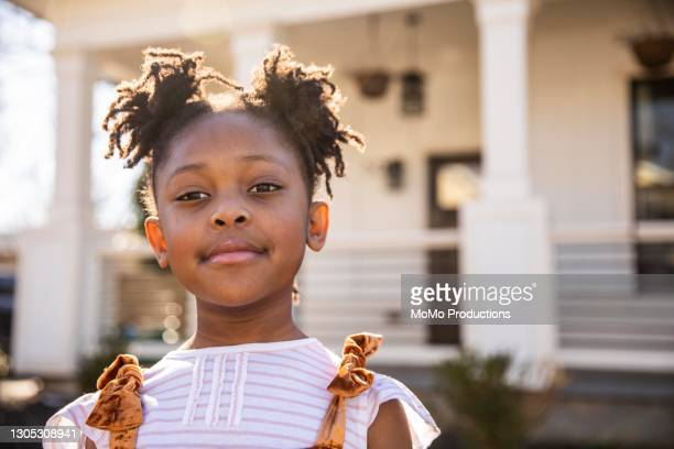portrait of young girl in front of home - primary age child stock pictures, royalty-free photos & images