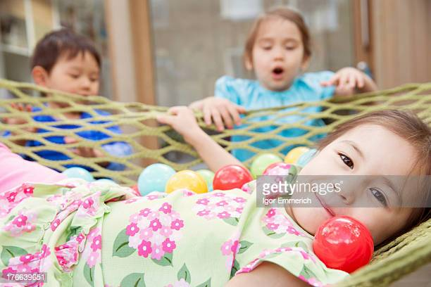 Portrait of young girl in hammock with colored balls
