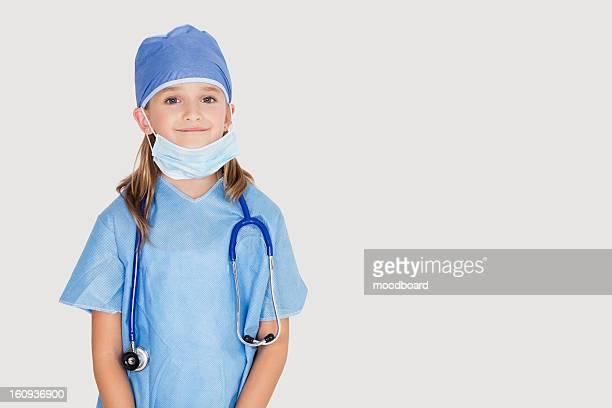 portrait of young girl in surgeon's costume against gray background - operatiekleding stockfoto's en -beelden
