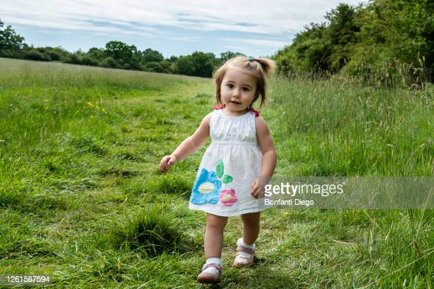 portrait of young girl in white dress walking on a meadow, looking at camera. - white dress stock pictures, royalty-free photos & images