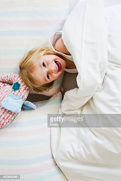 Portrait of young girl lying in bed with toy elephant