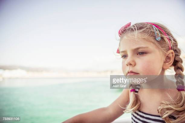 Portrait of young girl near water, pensive expression