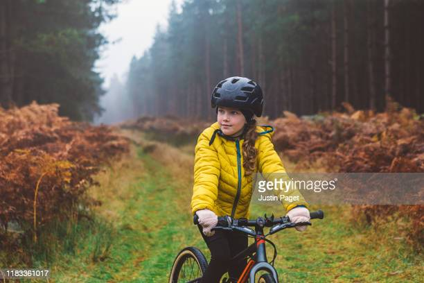 portrait of young girl on bike in forest - headwear stock pictures, royalty-free photos & images