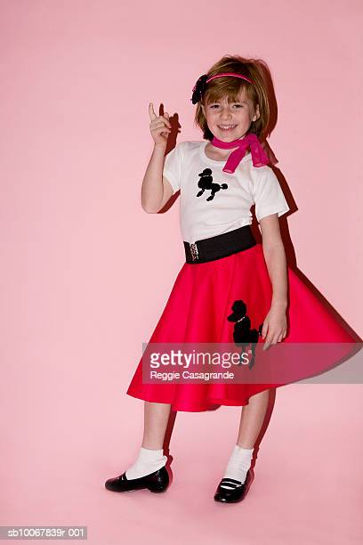 portrait of young girl (6-7) on pink background - poodle skirt stock photos and pictures