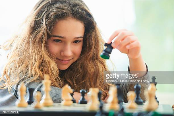 Portrait of young girl playing chess