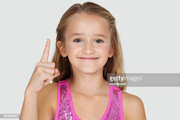 Portrait of young girl pointing upwards against gray background