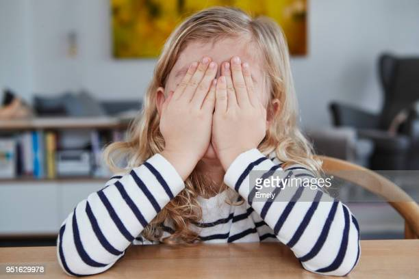portrait of young girl, sitting at table, covering face with hands - augen zuhalten stock-fotos und bilder