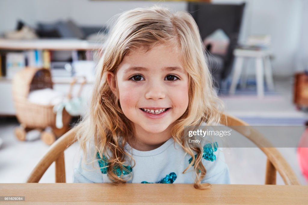 Portrait of young girl, sitting at table, smiling : Stock Photo