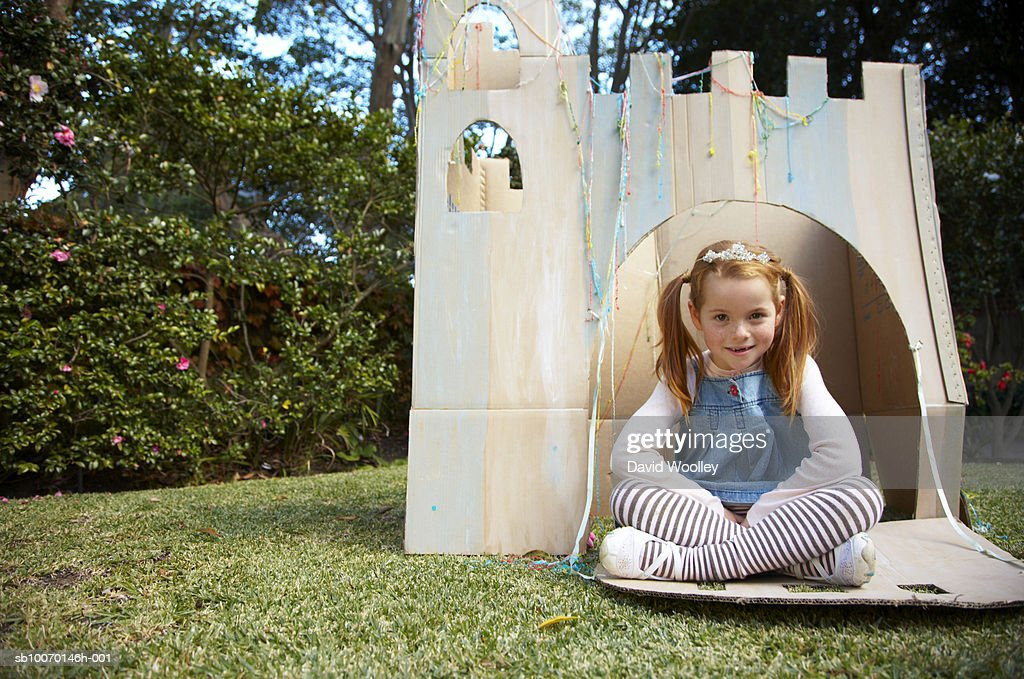 Portrait of young girl sitting in cardboard castle : Stock Photo