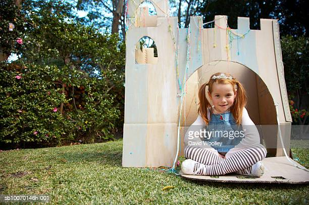 Portrait of young girl sitting in cardboard castle