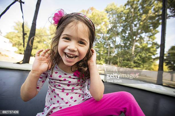 Portrait of young girl sitting on large trampoline, laughing