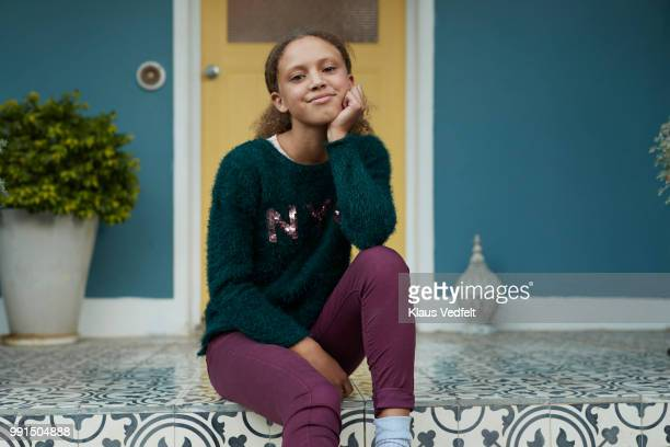 Portrait of young girl sitting on porch