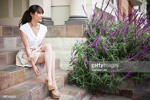 Portrait of young girl sitting on steps at home