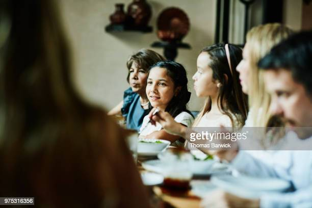 Portrait of young girl sitting with family at dinner table during celebration meal