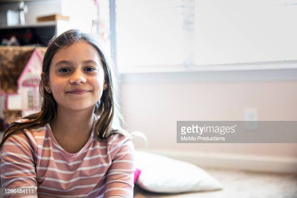 portrait of young girl smiling in her bedroom - latin american and hispanic ethnicity stock pictures, royalty-free photos & images