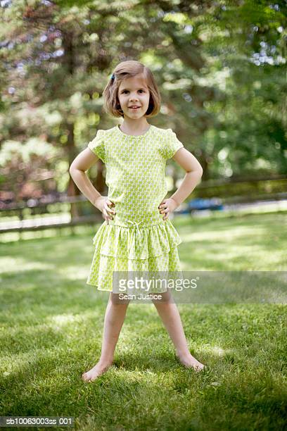 Portrait of young girl (6-7 years) standing on lawn with hands on hip