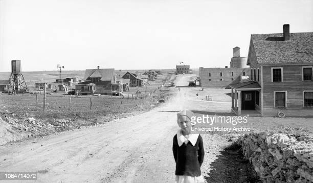 Portrait of Young Girl, Street Scene with Abandoned Grain Mill and Bank both right in Background, Mills, New Mexico, USA, Dorothea Lange, Farm...