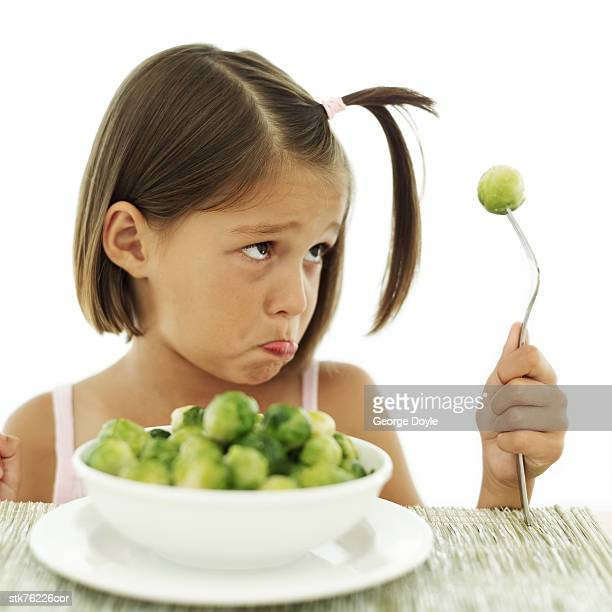 portrait of young girl sulking at a bowl of vegetables