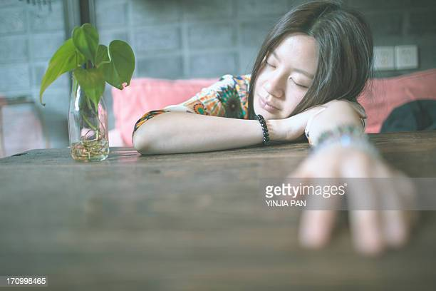 Portrait of young girl taking a nap in cafe