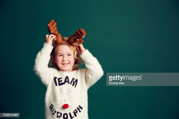Portrait of young girl wearing Christmas and reindeer antlers